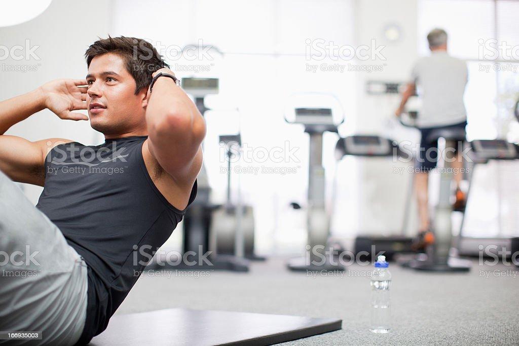 Smiling man doing sit-ups in gymnasium royalty-free stock photo