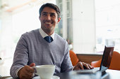 Smiling man drinking coffee in cafe