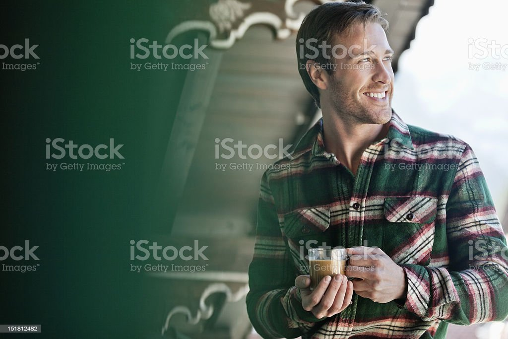Smiling man drinking coffee on cabin porch royalty-free stock photo