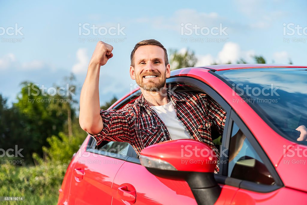 Smiling man driving a new car. stock photo