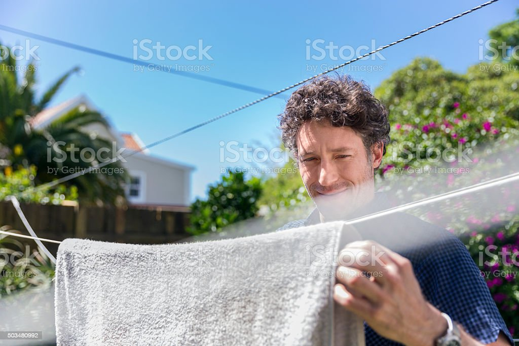 Smiling man drying towel in yard stock photo