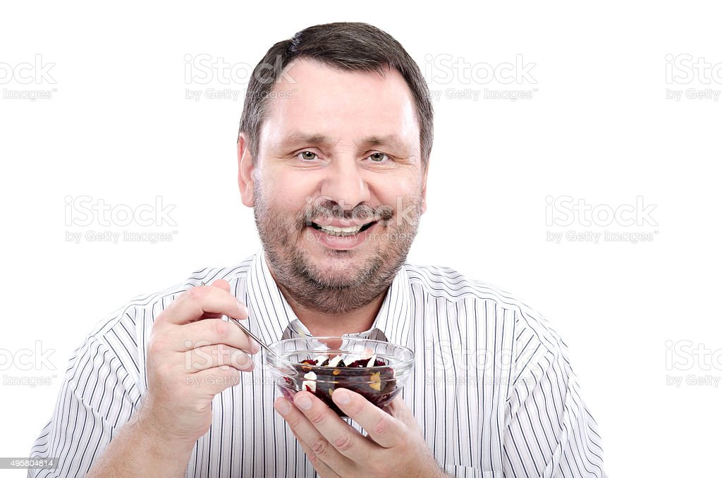 Smiling man eating a beet salad stock photo