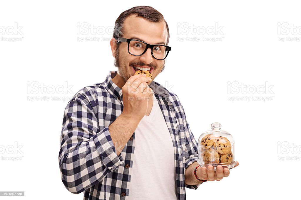 Smiling man eating a cookie stock photo