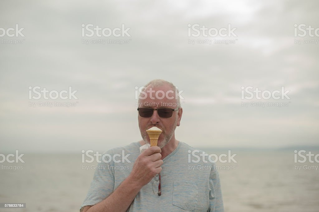 Smiling  man eating ice-cream by the ocean stock photo