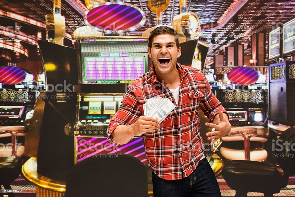 Smiling man excited by money in casino stock photo