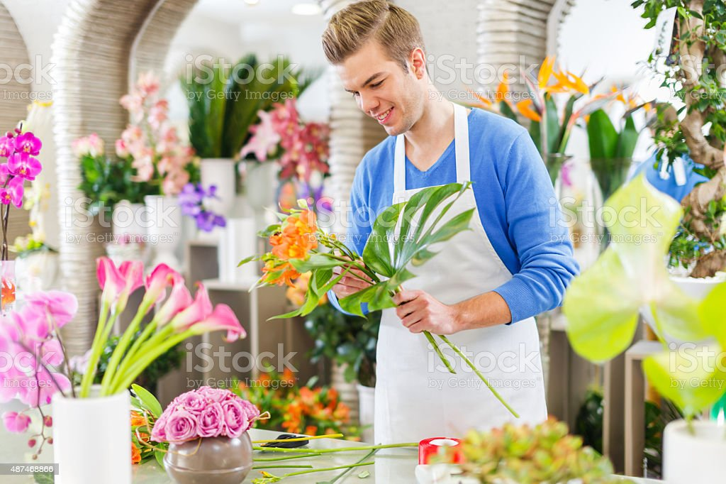 Smiling man florist making flower arrangement in flower shop. stock photo
