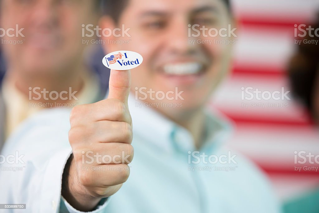 Smiling man gives thumbs up with an I voted sticker stock photo