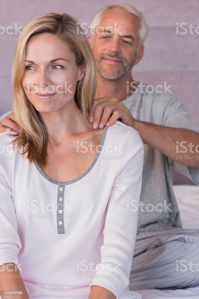 Smiling man giving massage to his wife royalty-free stock photo