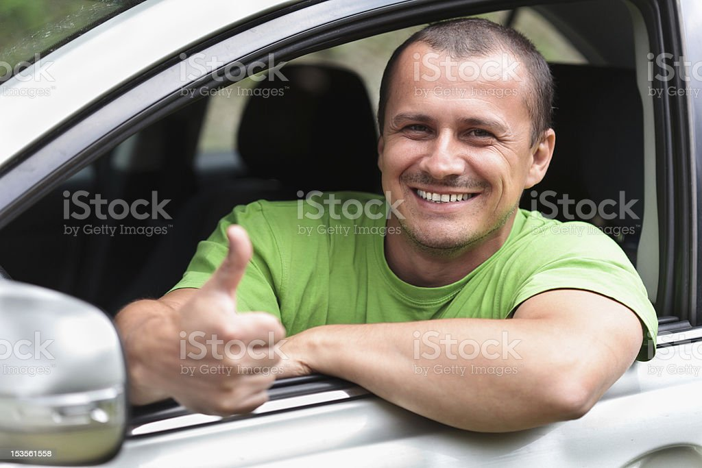 Smiling man giving thumbs up from inside his new car royalty-free stock photo