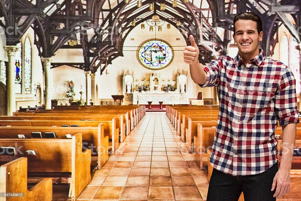 Smiling man giving thumbs up in church stock photo