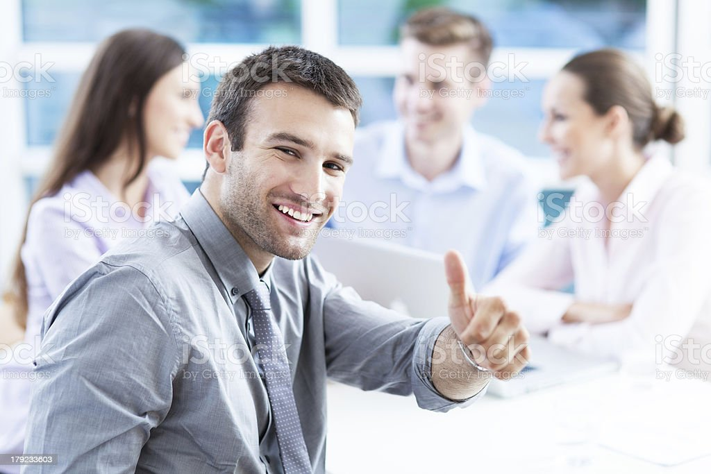 Smiling man giving thumbs up with colleagues blurred royalty-free stock photo