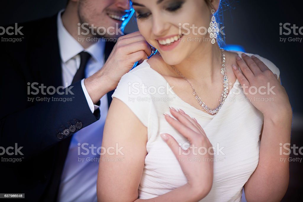 Smiling man giving woman elegant necklace stock photo