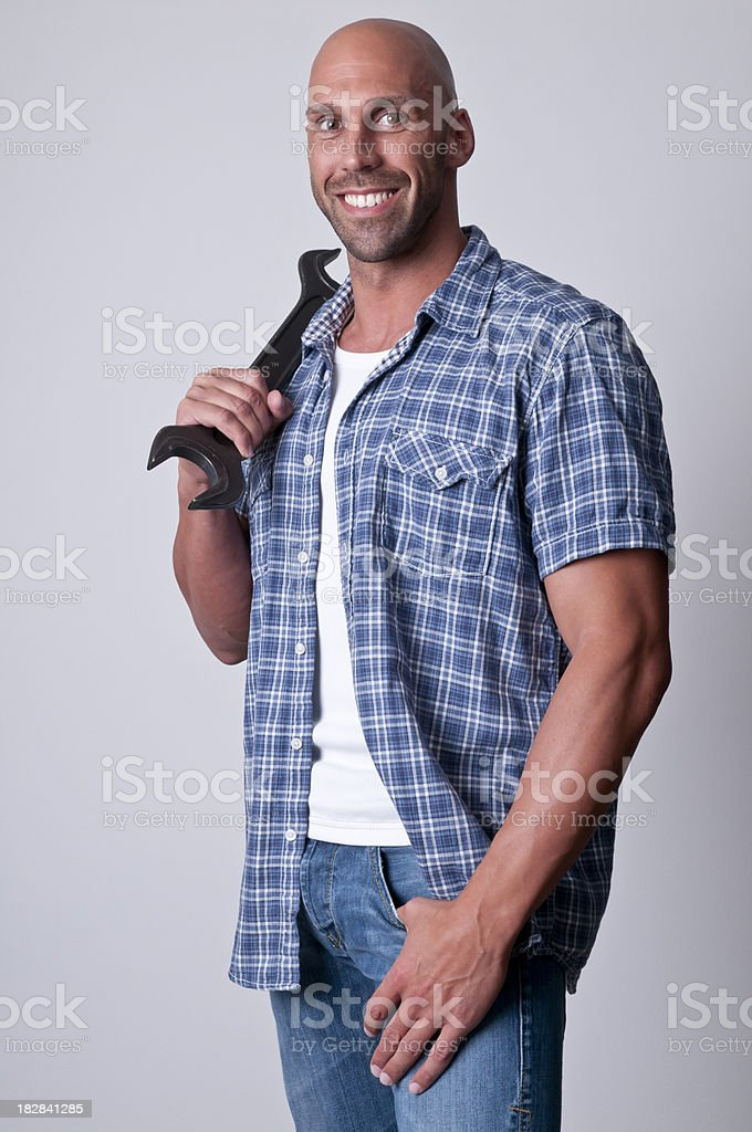 smiling man holding a wrench royalty-free stock photo