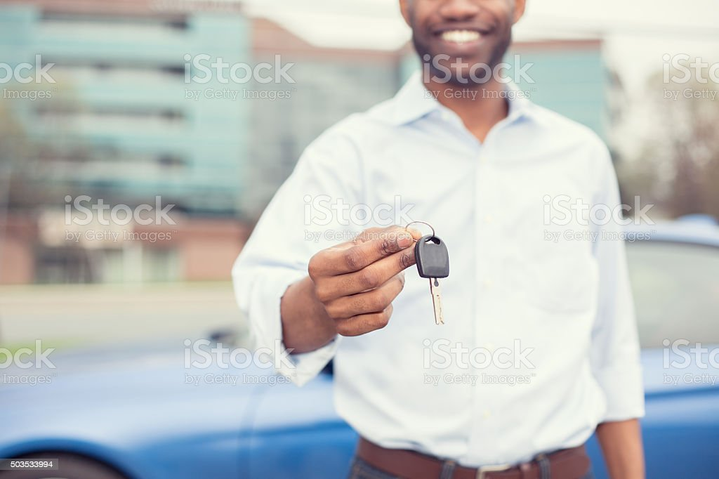 Smiling man holding car keys offering new blue car stock photo