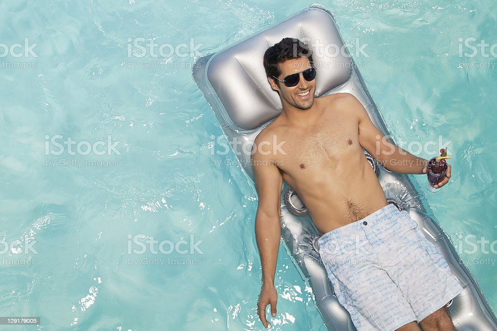 Smiling man holding glass while lying on raft royalty-free stock photo