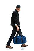 Smiling man holding gym bag and walking