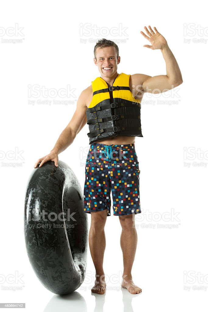 Smiling man holding inner tube and waving hand stock photo