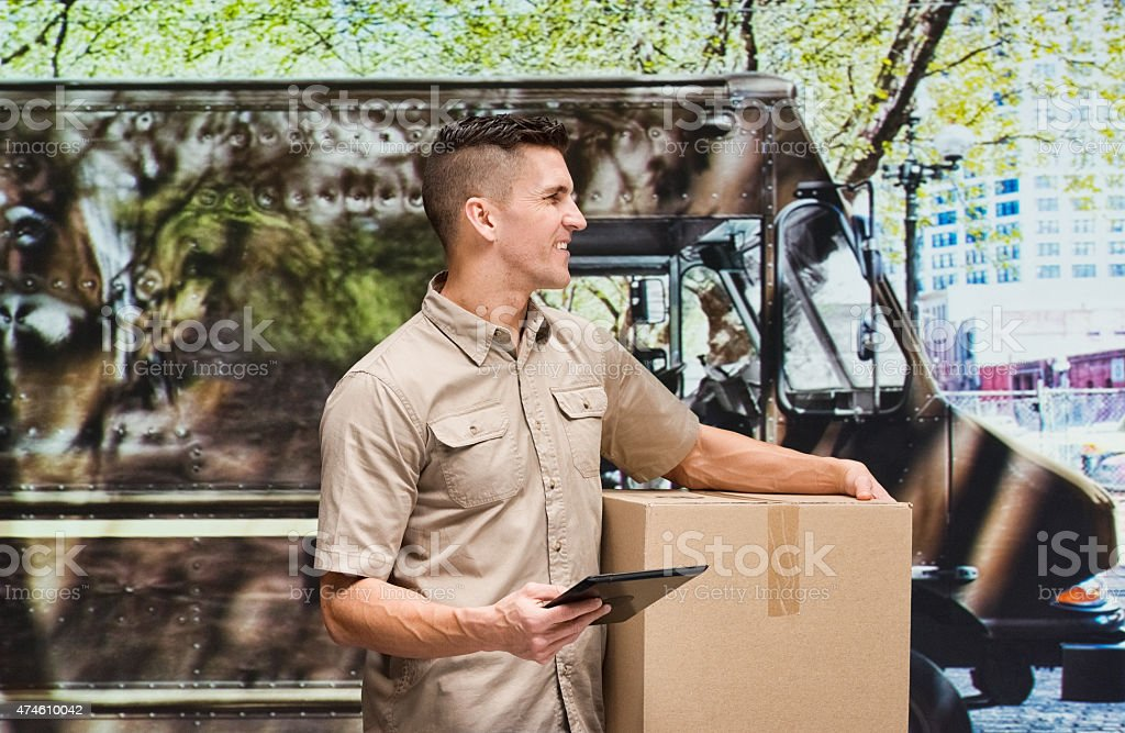 Smiling man holding package and tablet outdoors stock photo