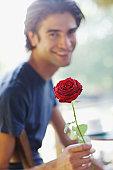 Smiling man holding red rose