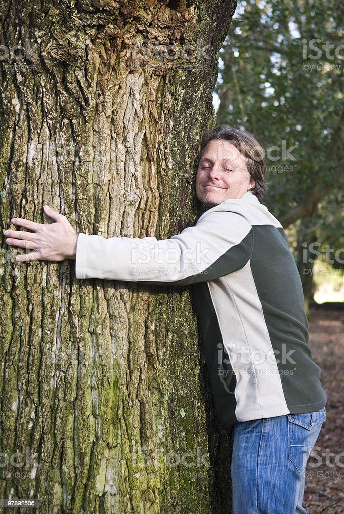 smiling man hugging tree royalty-free stock photo
