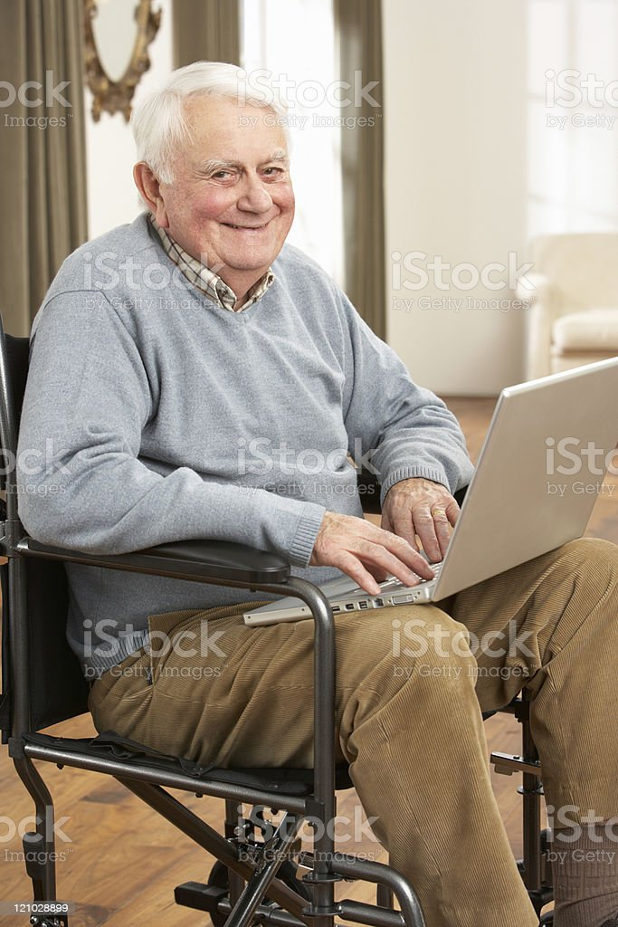 Smiling man in a wheelchair using laptop royalty-free stock photo
