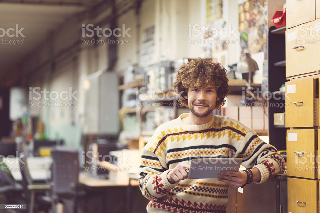 Smiling man in a workshop, using a digital tablet stock photo