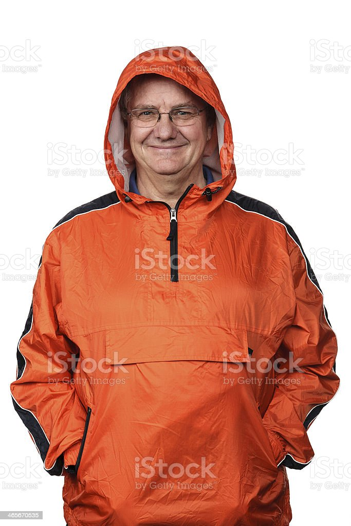 Smiling man in an orange rain jacket with hood. royalty-free stock photo