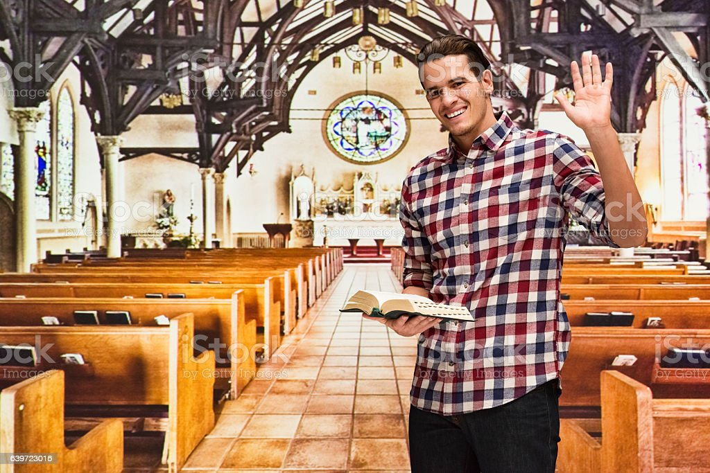 Smiling man in church and waving hand stock photo