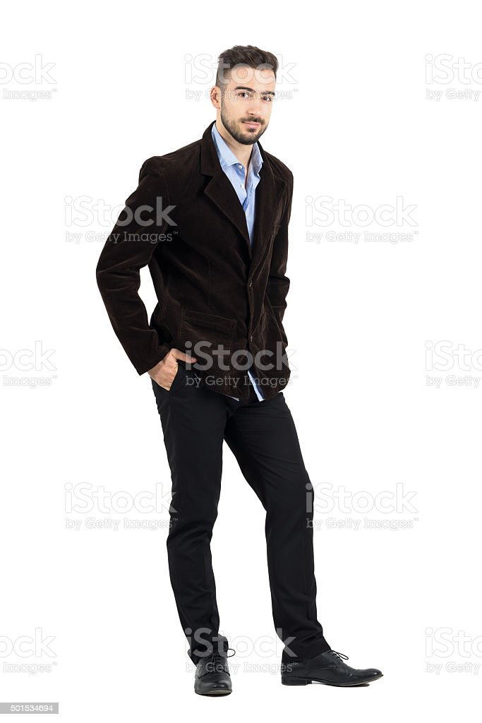 Smiling man in corduroy coat with hands in pocket stock photo