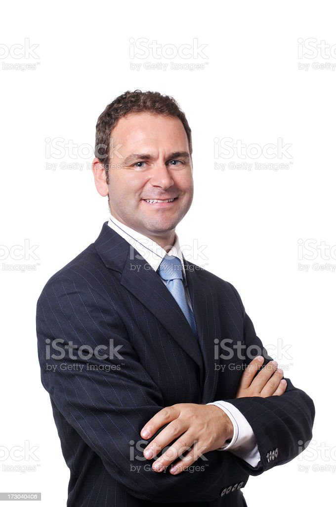 Smiling man in dark business suit and tie folding his arms stock photo