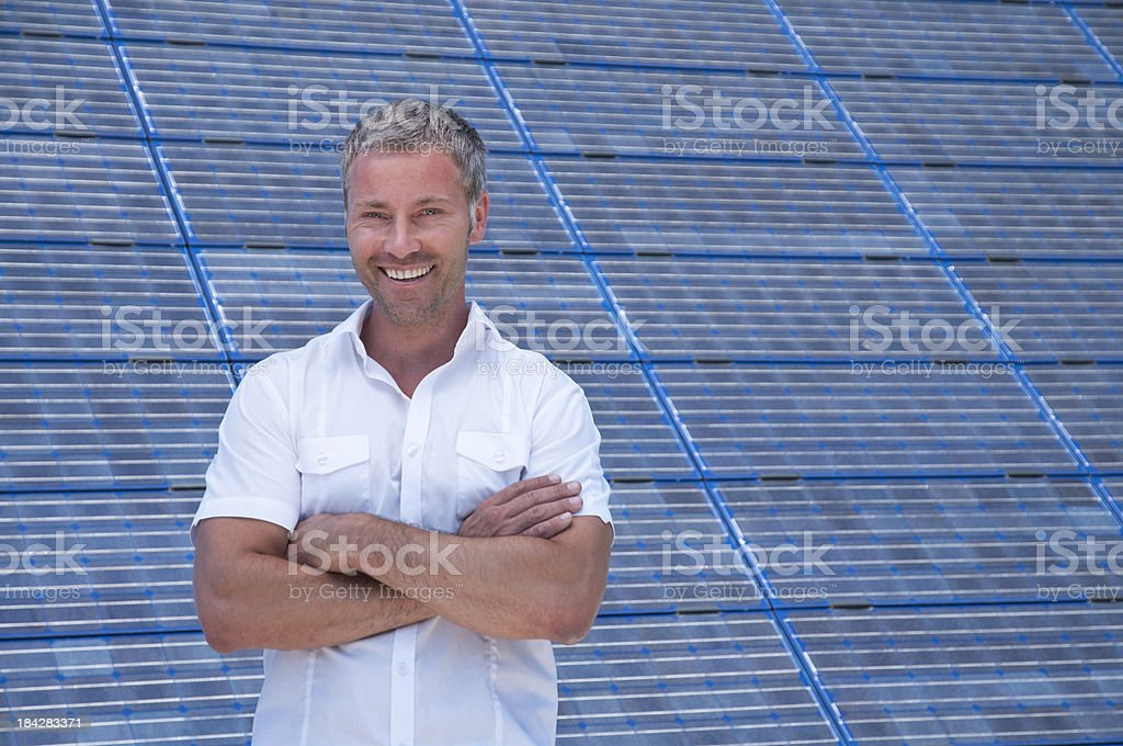 smiling man in front of a solar power station royalty-free stock photo