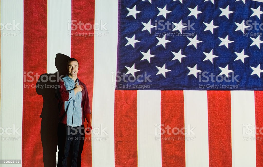 Smiling man in front of American flag stock photo