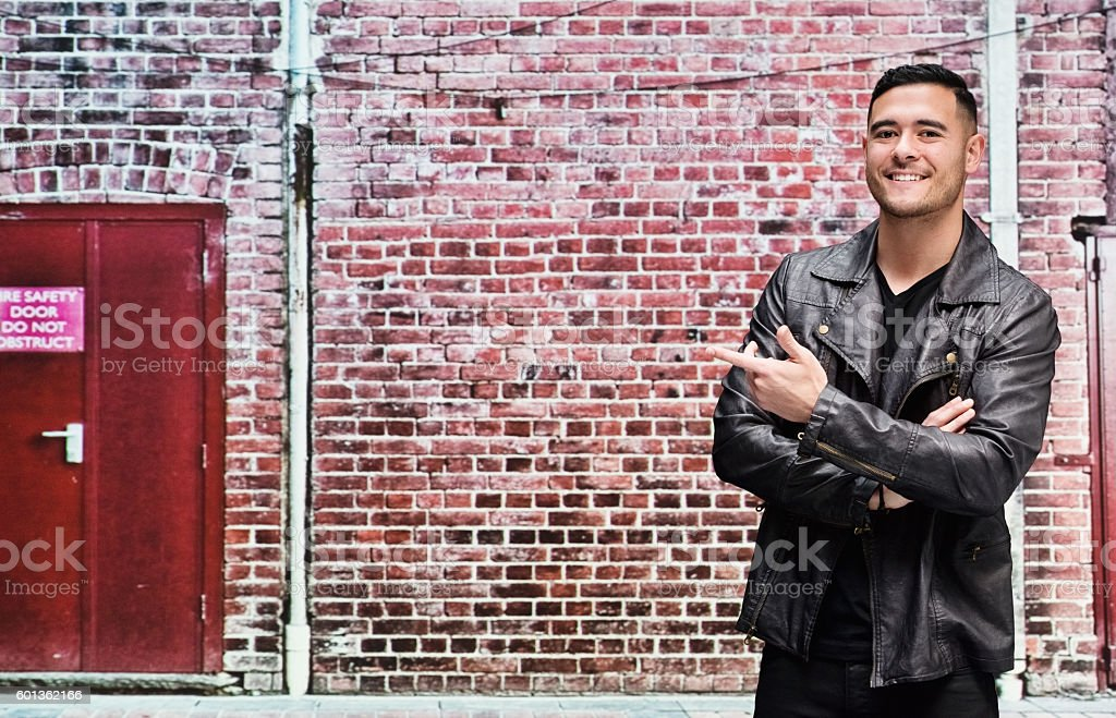 Smiling man in front of brick wall and pointing stock photo