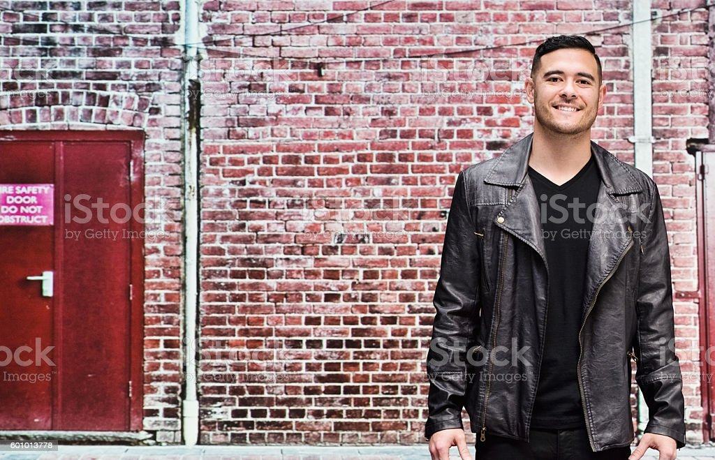 Smiling man in front of brick wall stock photo