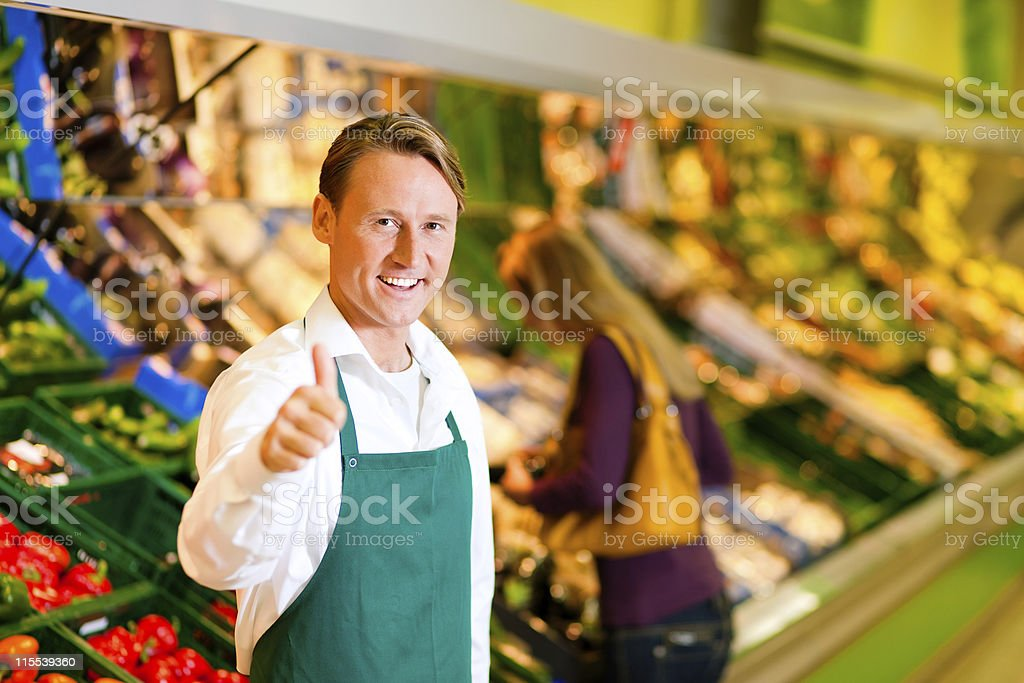 Smiling man in green apron with one thumb up at supermarket stock photo