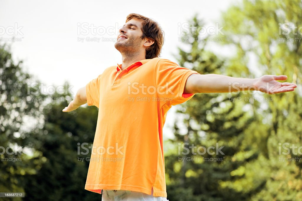 Smiling man in orange shirt with arms wide open outdoors stock photo