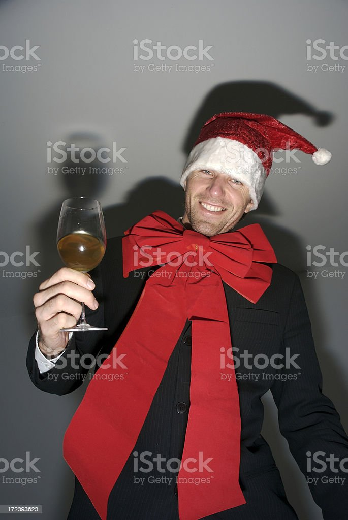 Smiling Man in Santa Hat Parties with Wine Glass stock photo