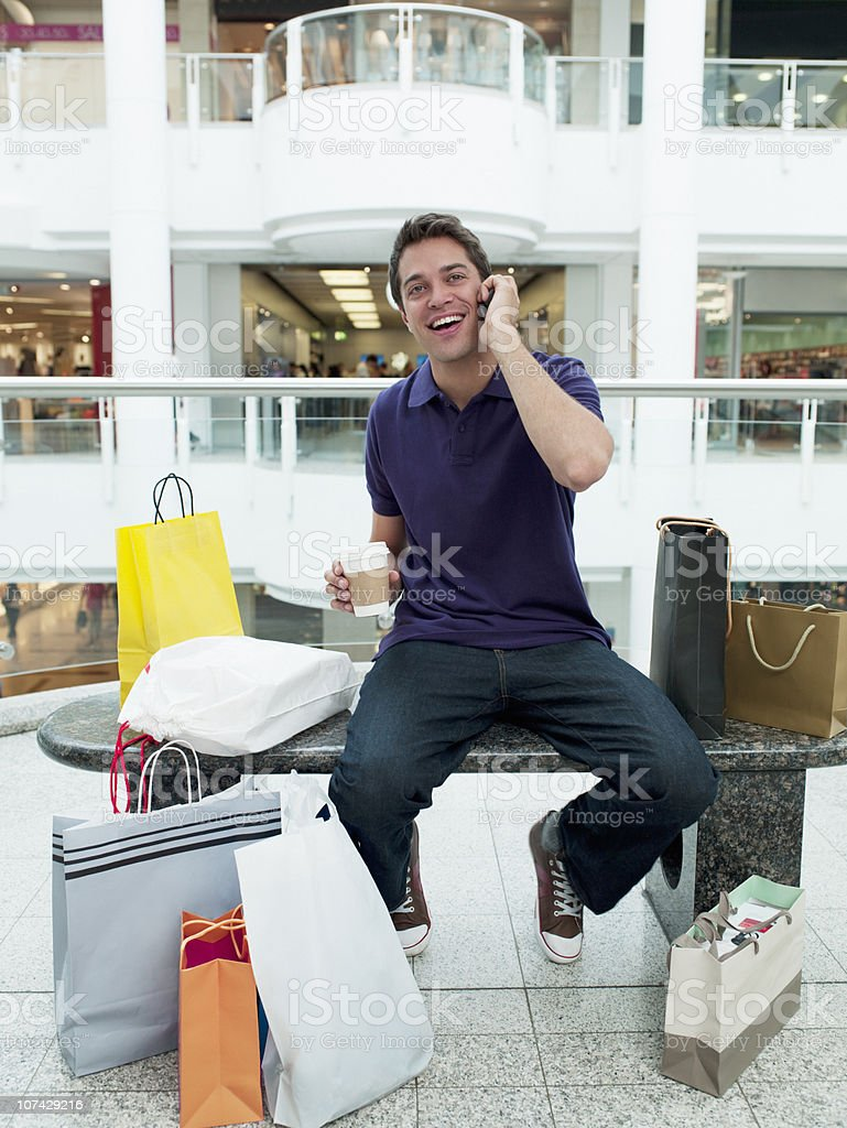 Smiling man in shopping mall talking on cell phone royalty-free stock photo