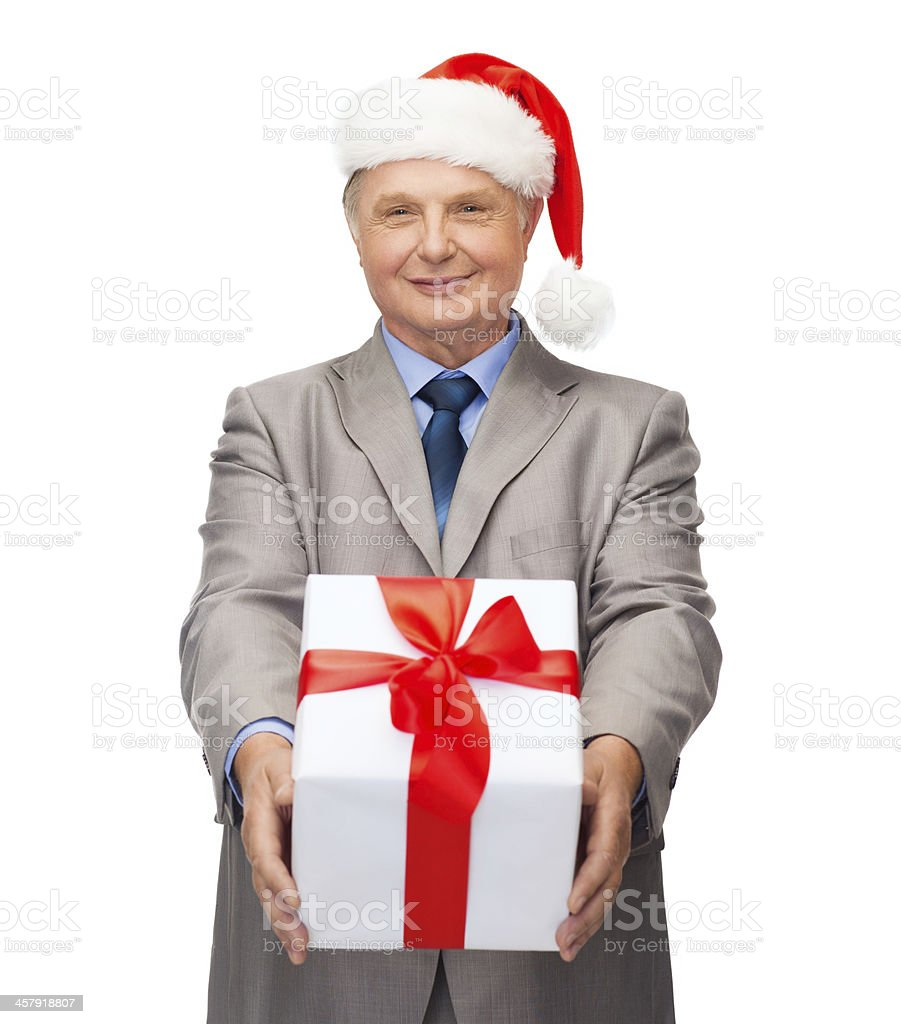 smiling man in suit and santa helper hat with gift stock photo