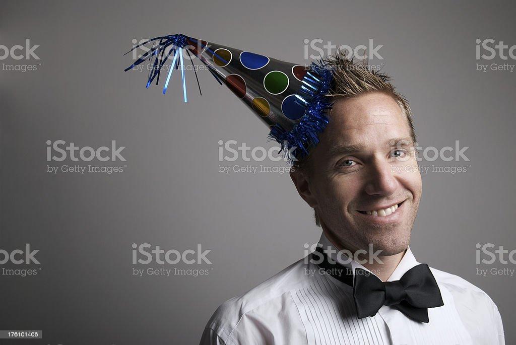 Smiling Man in Tuxedo Celebrating Wearing Party Hat royalty-free stock photo