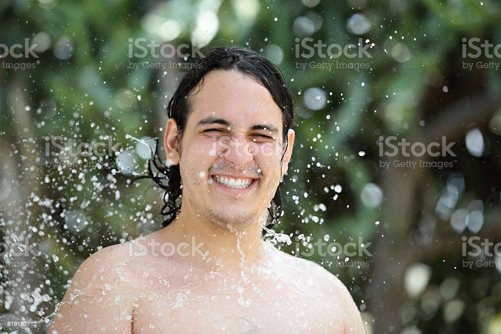 smiling man in water splashes stock photo