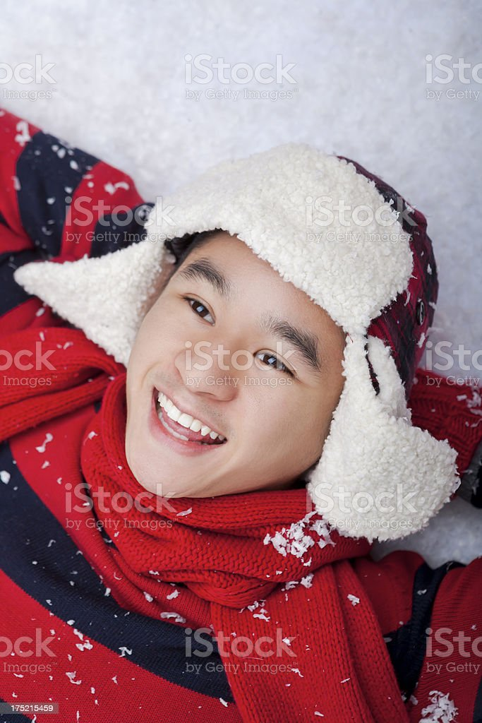 Smiling man laying on the snow royalty-free stock photo