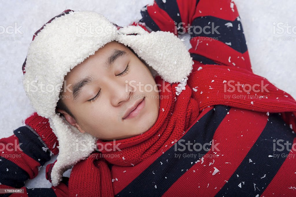 Smiling man laying on the snow stock photo