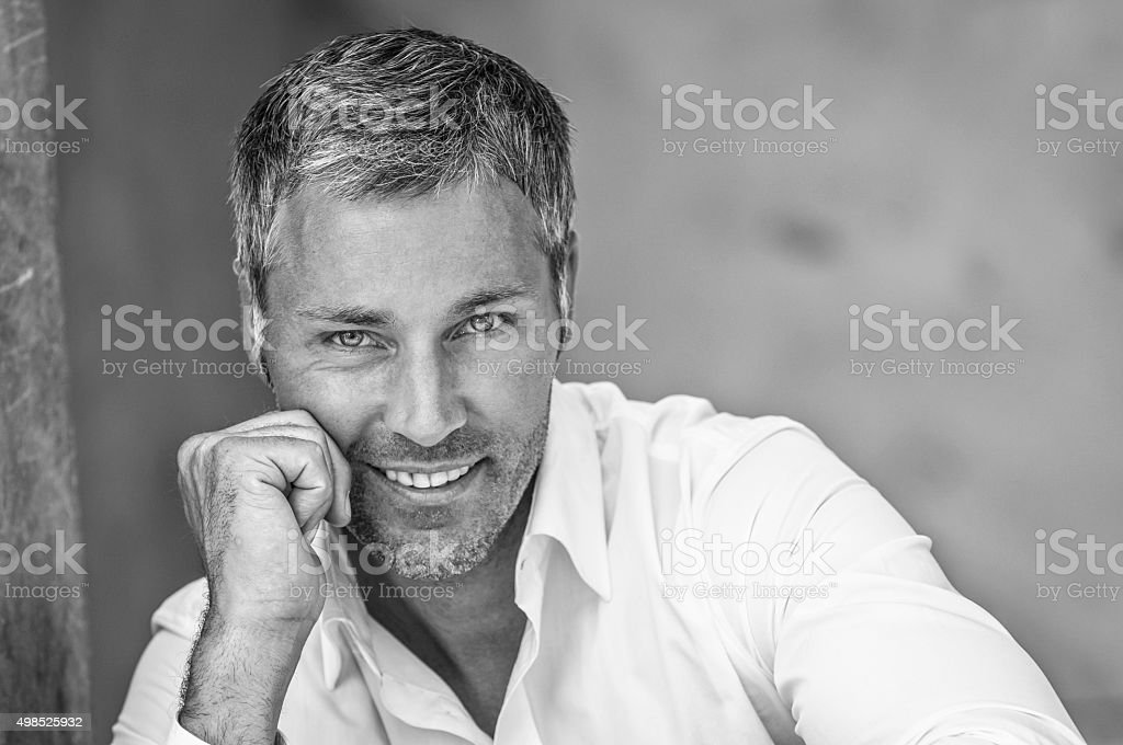 smiling man leaning on his hand stock photo