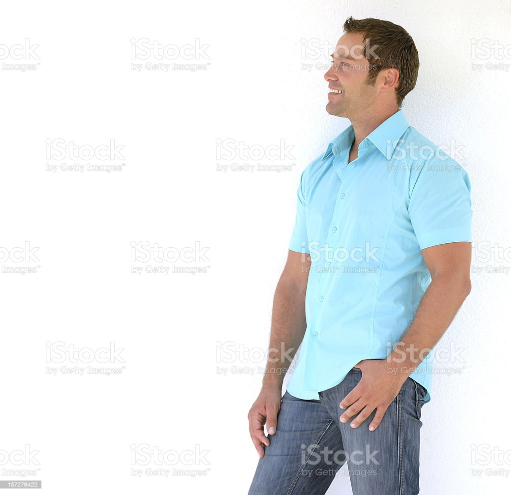 Smiling man leaning up against a wall stock photo