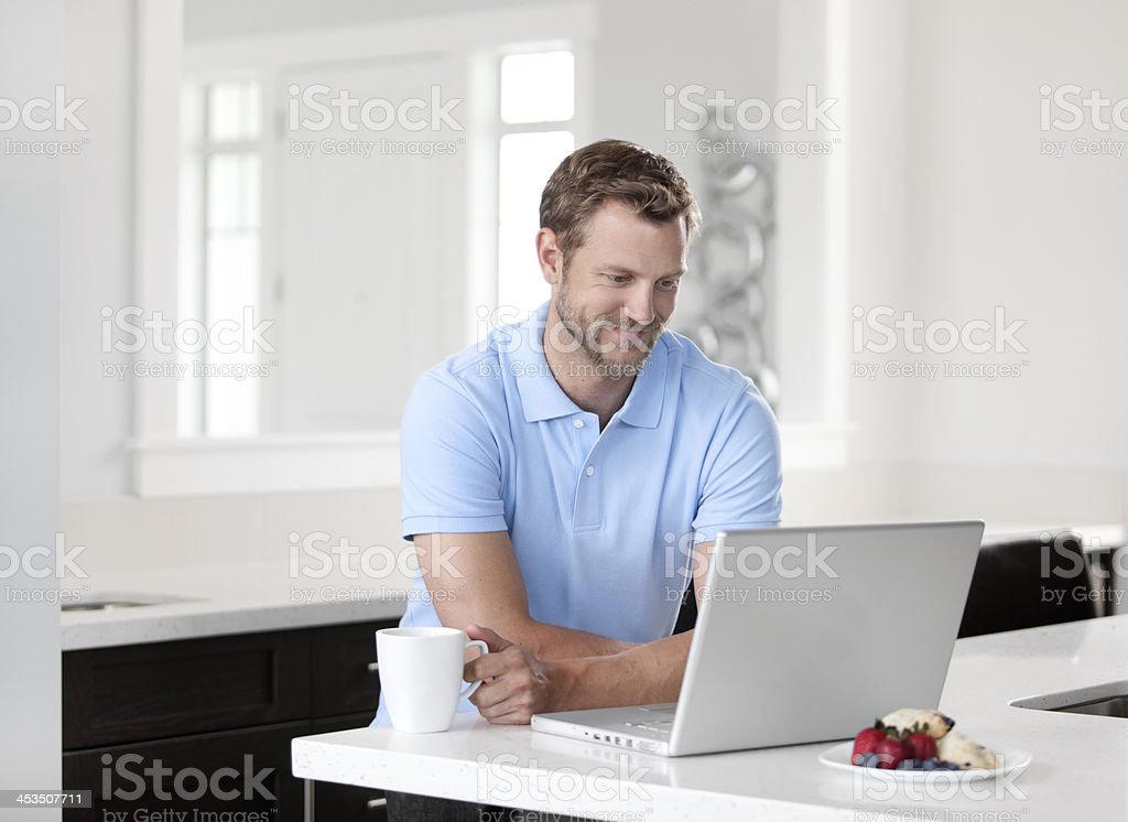 Smiling man looking at his computer stock photo