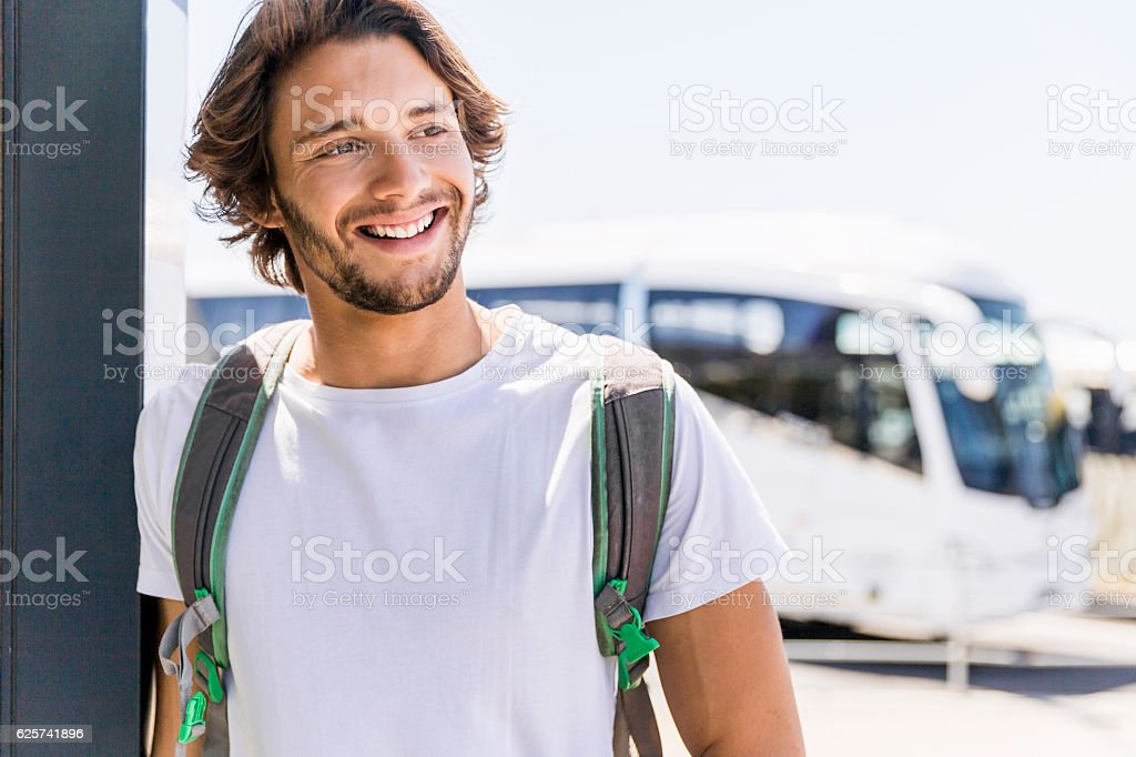 Smiling man looking away while leaning on wall stock photo