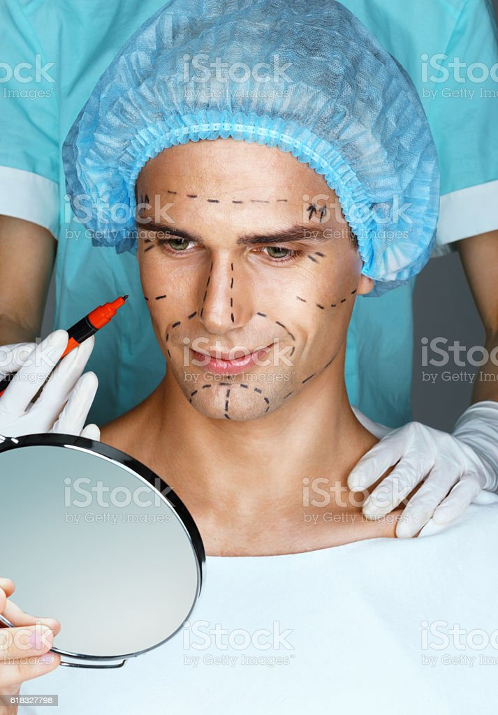 Smiling man looking in the mirror stock photo