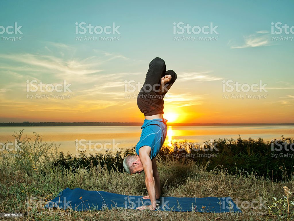 smiling man making yoga exercises outdoors stock photo
