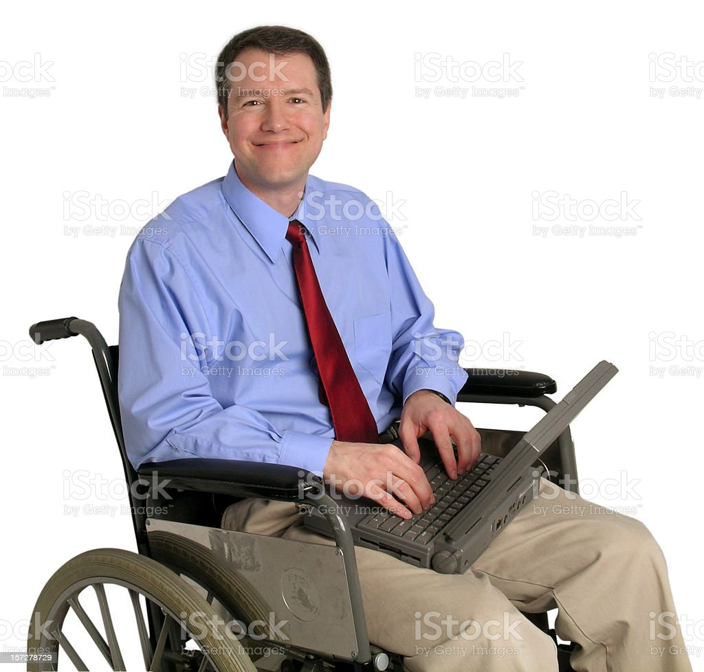 Smiling man on a wheelchair using vintage laptop royalty-free stock photo